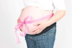 Belly of pregnant woman with pink bow